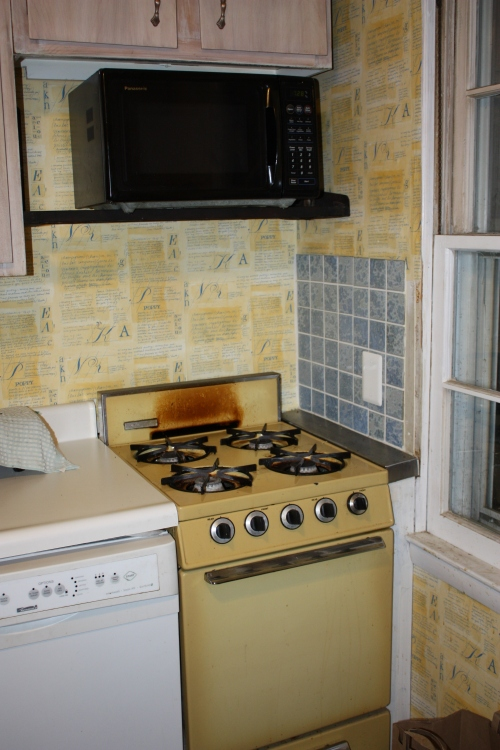 Our old yellow apartment-sized stove and oven with four burners.