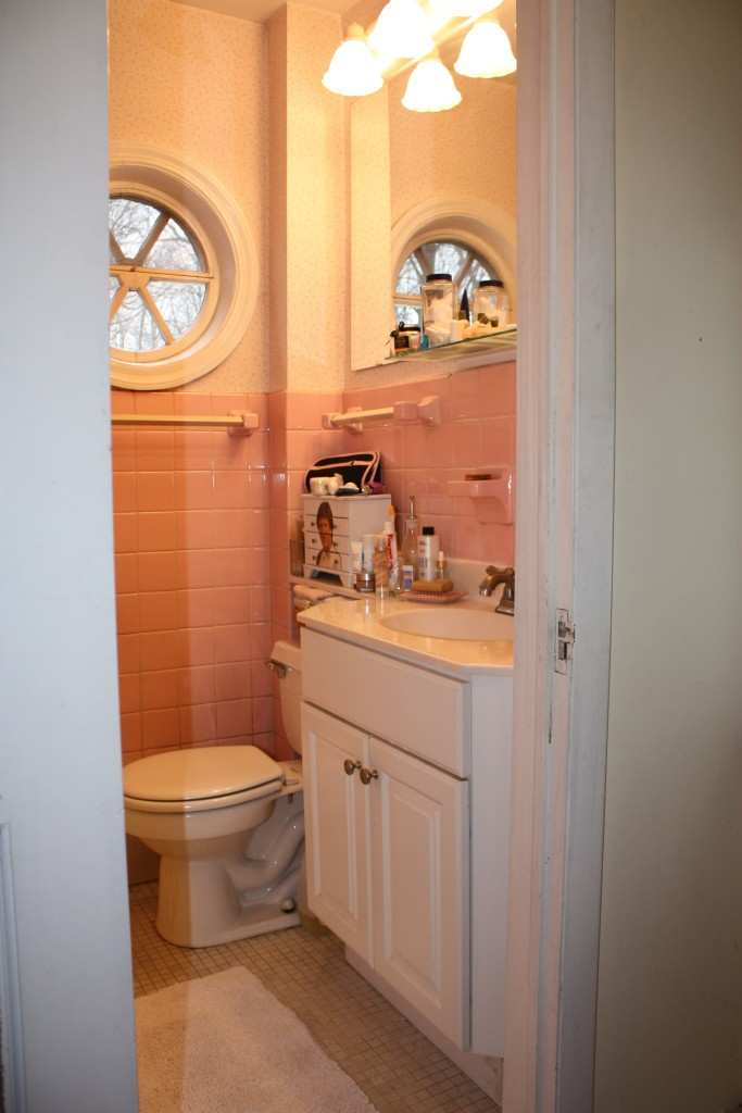 Our tiny original bathroom has pink and white wallpaper above the pink tile.