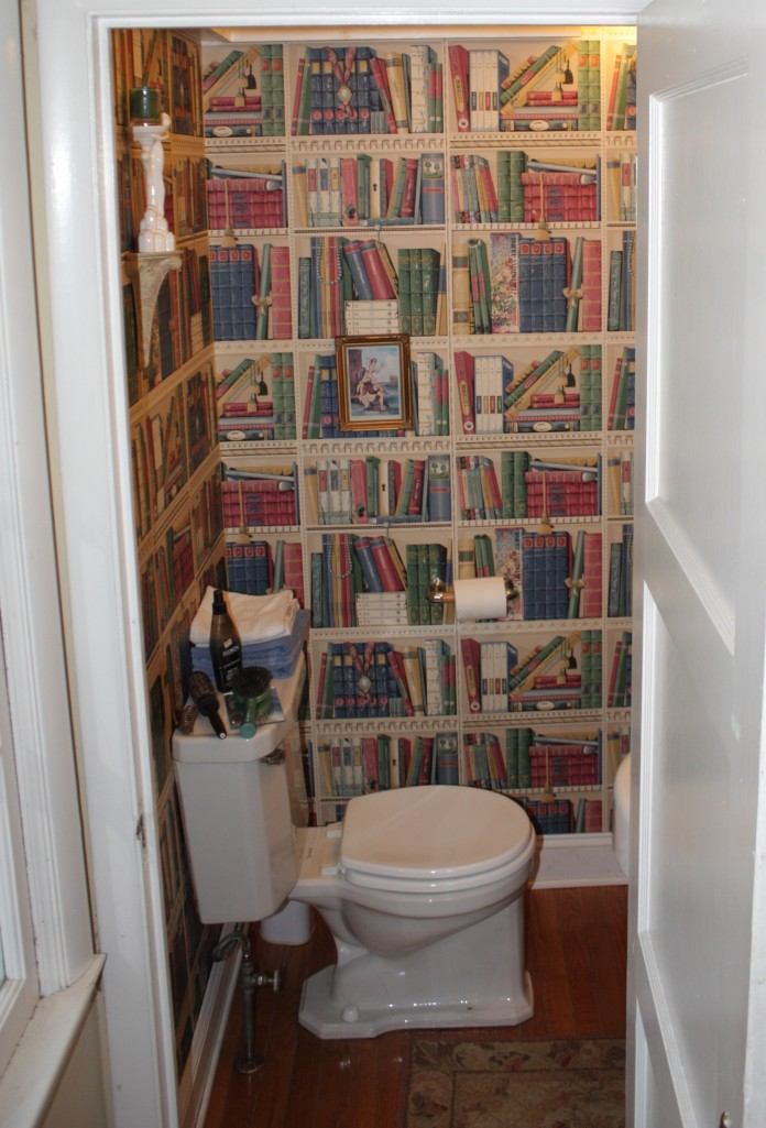 Our tiny powder room is papered with faux bookshelves.