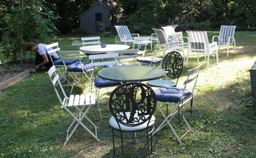 Tables and chairs set up in the back yard.