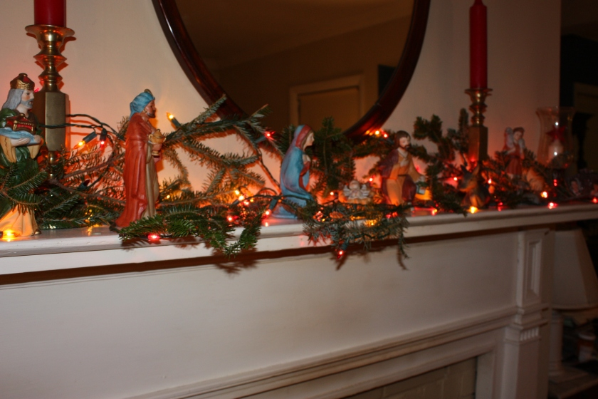 The mantel display from 2011 included a crèche, fresh pine boughs, and lights.