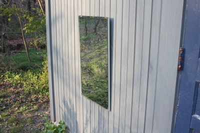A plain old mirror hangs on the front of the shed. Maybe I can find another one for the side porch.