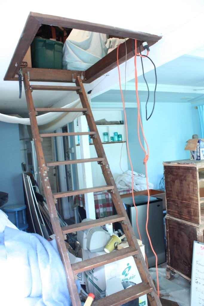 This permanent ladder leads to the cottage attic and tucks up near the ceiling.