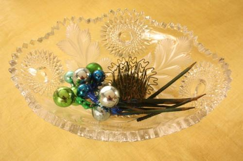 A crystal bowl with some glass Christmas balls on picks and a hairpin flower frog.