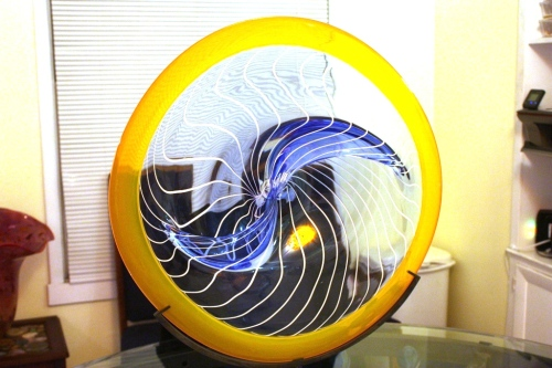 Yellow and blue swirled plate has about an 18 inch diameter.