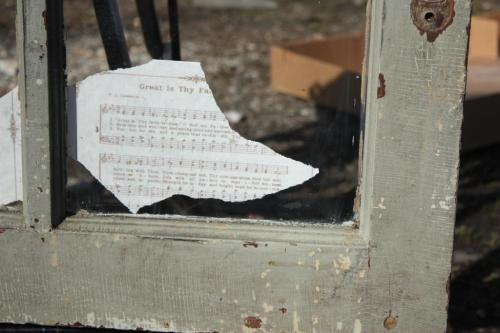 The paper is glued to the back of the window with the writing showing through to the right side.