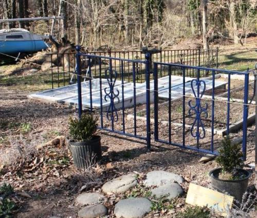 A section of fence and the gate painted navy blue