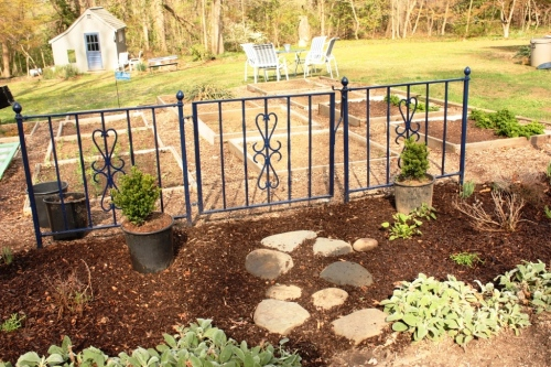 A wrought iron fence gives structure to the front of the potager.