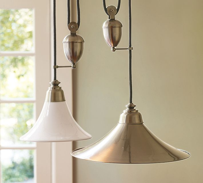 Pottery Barn Porter pendants have a rise and fall mechanism.  I would choose a combination of sizes in the metal finish.