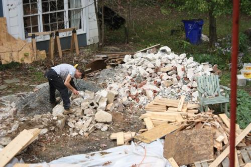 Piles of lumber, rubble and building debris filled the space between the cottage and the house.