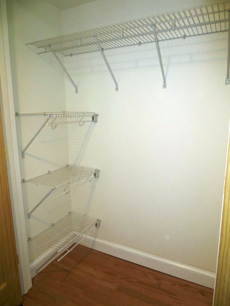 The long shelf is 16 inches wide with a hanging bar at the 12-inch mark unlike the narrower shelves on the side.