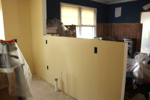 This knee wall will have dark grey cabinets on the bottom, a stainless steel countertop, and grey limestone backsplash to the cap of the wall.