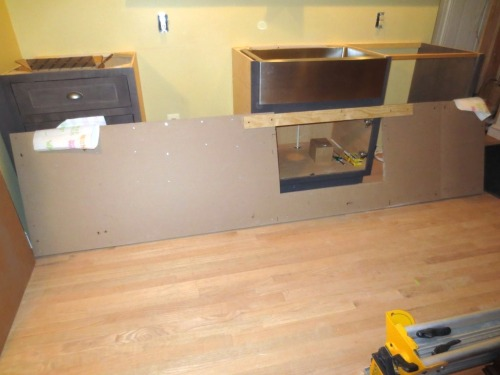 The substrate for the countertop is leaning against the cabinets.