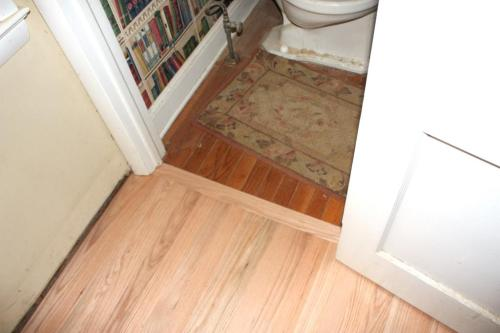 The transition between the powder room and the front hall will disappear when the new floor is finished.