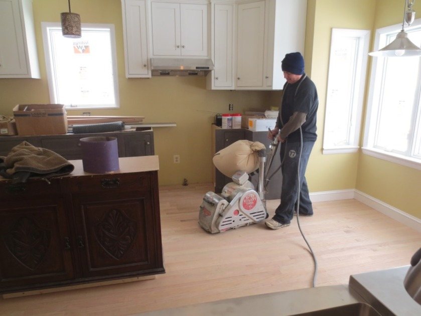 Professional floor installers put in the kitchen floor from beginning to end.