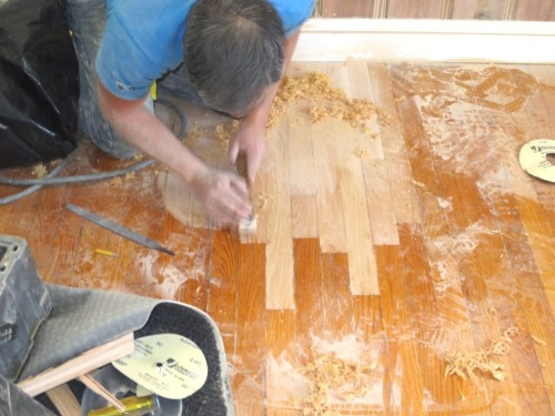 Hand-scraping blends the new floor boards into the old without removing the finish from the old floor.