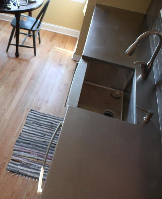 The stainless steel counter and deep sink are ready for service.