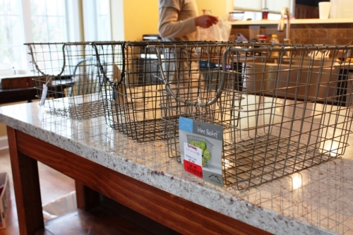 Wire baskets tie into the hardware and stainless steel finishes in the kitchen.