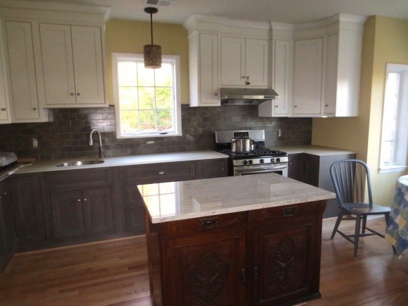 The kitchen cabinets are dark grey on the bottom and white uppers.