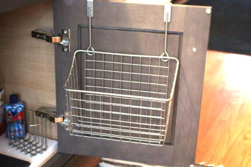 A wire basket that hangs over the cabinet door.