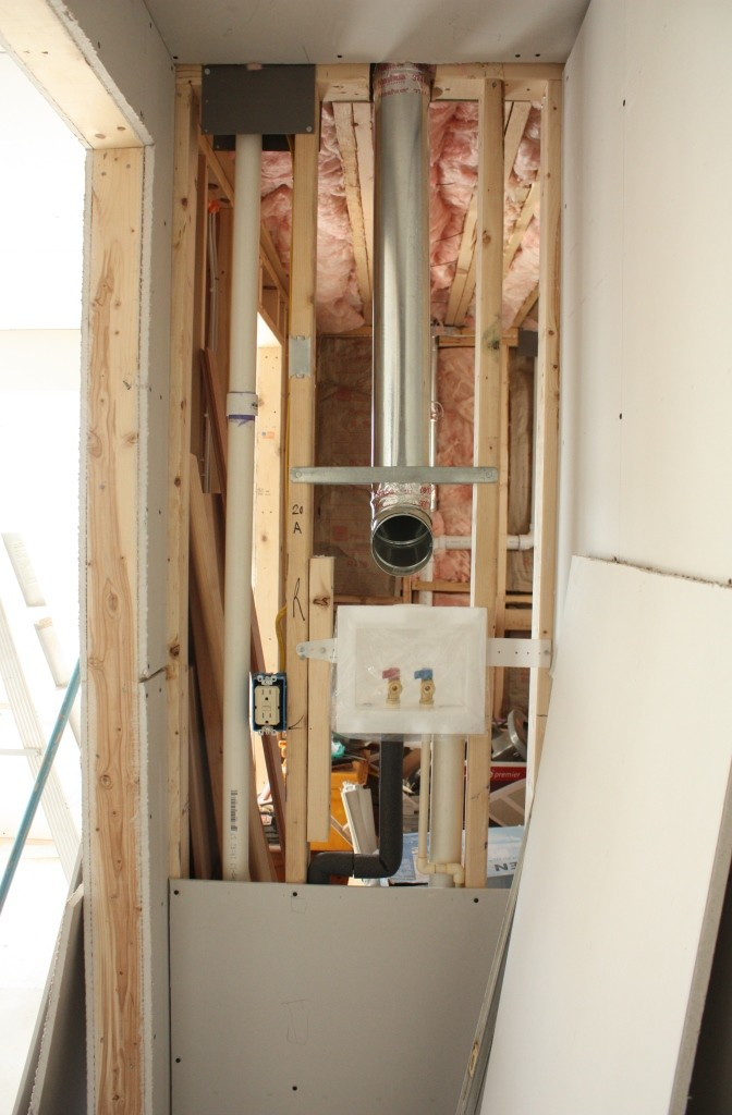 Looking from the closet side, the wall in the bathroom is loaded with pipes and vents.