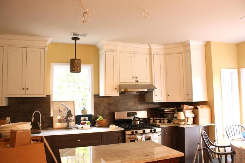 Wires hanging over the kitchen island are waiting for hanging pendants.