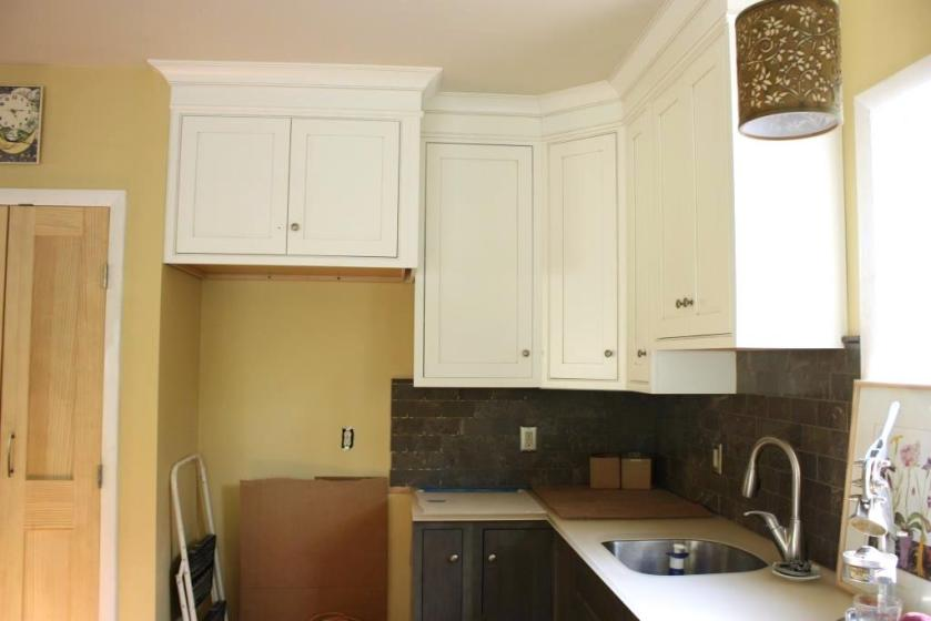 """The new refrigerator which we've been """"storing"""" in the dining room is supposed to fit in the niche where the short ladder and corrugated cardboard are resting."""