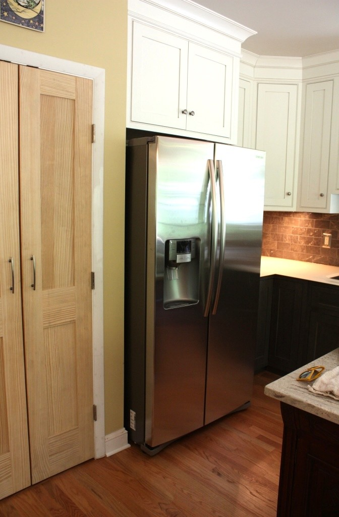 The odd cabinet is mostly unseen tucked to the right of the refrigerator.