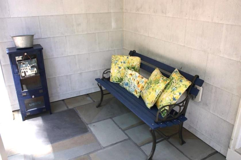 "Porch pillows on the bench say ""Spring is here."""