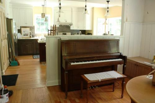 The kitchen is beyond the piano wall and in full daily use.