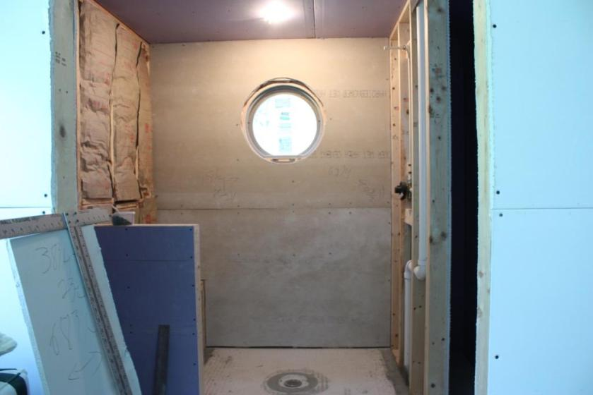 The conservatory bathroom has only the 24-inch round window, otherwise it is brightened by a recessed light in the shower and a wall fixture over the sink.