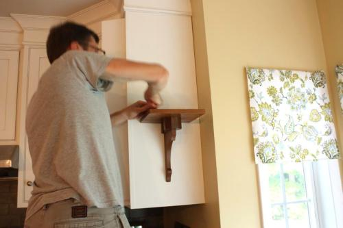 Charlie tightened the screws after the shelf was hung.