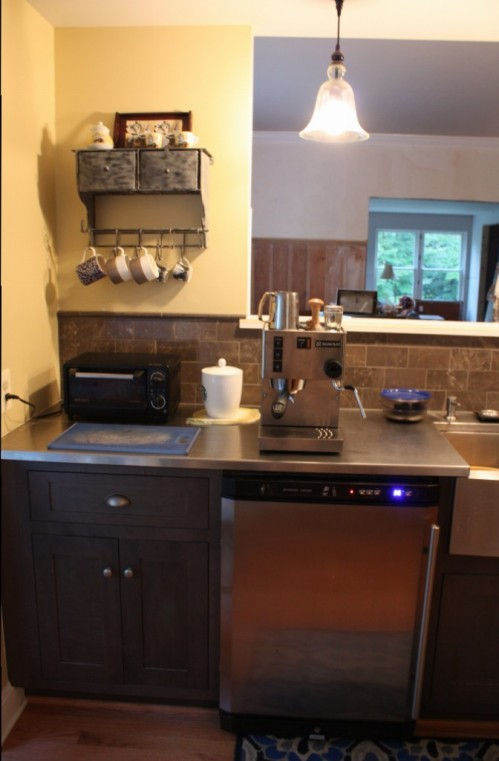 Utensils cups and coffee are in the cabinet, milk in the refrigerator, and espresso machine ready for action.