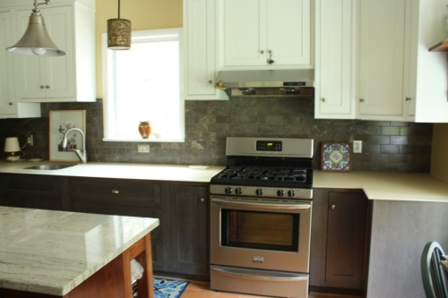 The bottom cabinets are dark grey stain and the top cabinets are white with a hint of grey wash in the bead.