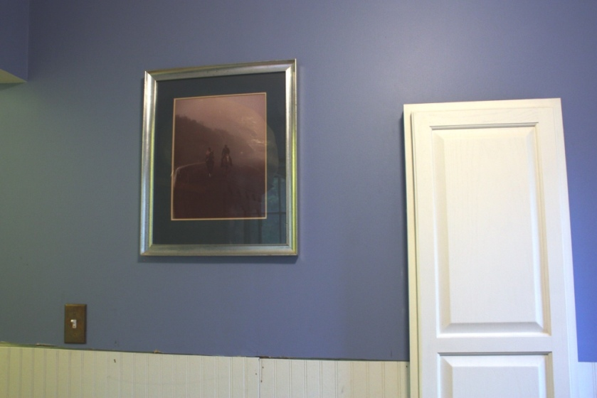 The photo is hanging next to the in-wall ironing board.