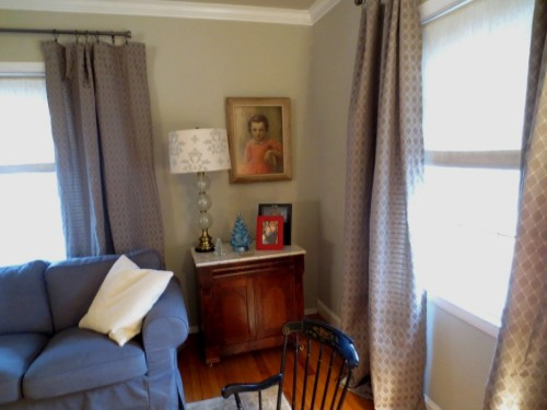 The front corner of the living room has an antique washstand topped with a lamp and some photos and my childhood pastel portrait hanging above.