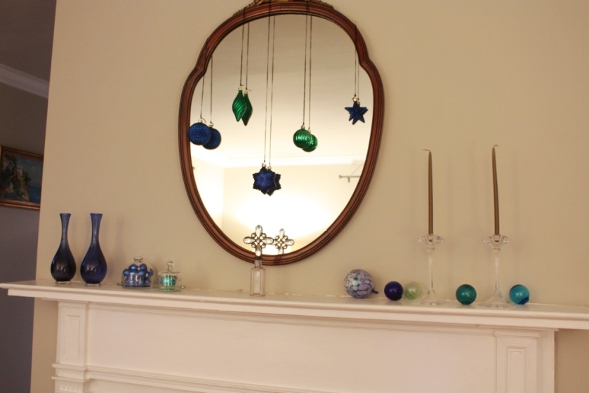 The mantel is very simple: blue and green balls hung from the mirror and stuffed into small cloches.