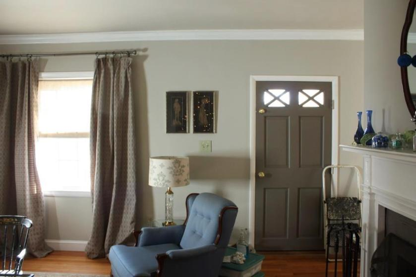 A pair of brass rubbings are hanging between the front door and the window over the light switch.