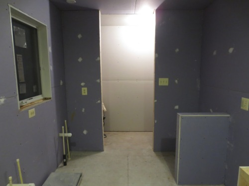 Looking out from the shower area, the floor will be tiled to the doorway (which will not have a door) then be wood in the hallway beyond.