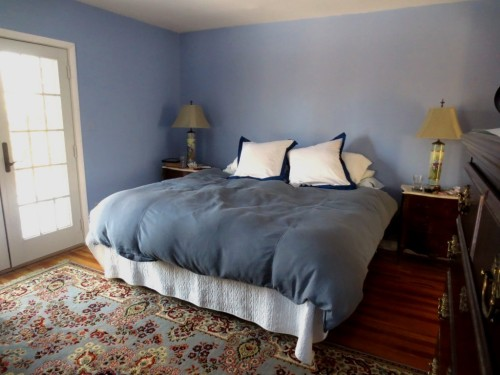 The current linens include a charcoal grey duvet cover and navy-timmed pillow covers.