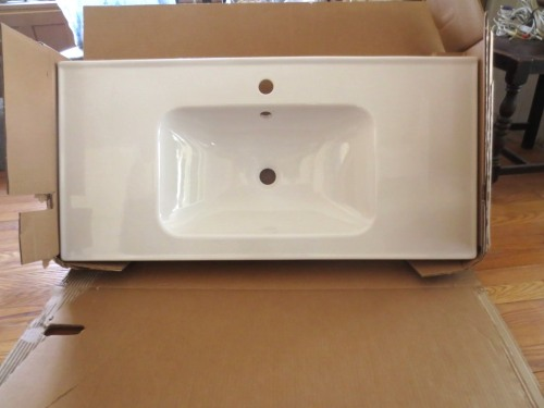 Porcelain sink with raised edges to contain the water.
