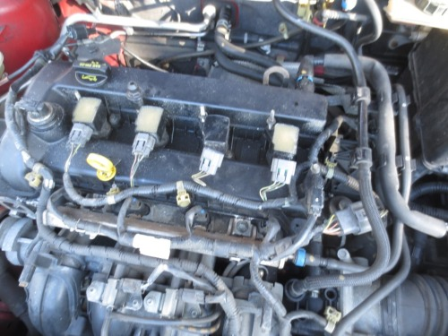 Spark plugs are hiding under the 4 rectangles (3 white, one black) lined up in  the center of the engine.