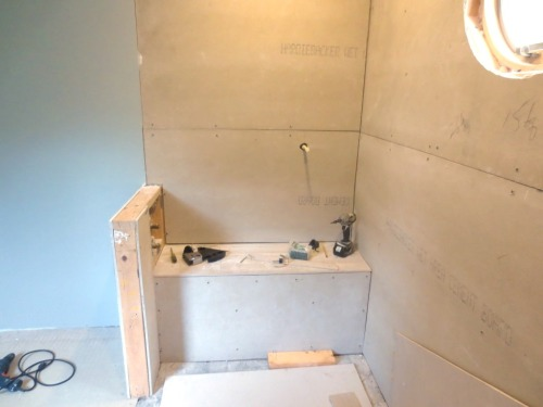 The controls in the master are in the knee wall on the left and the hand-held sprayer position is to the right on the wall behind the shower bench.