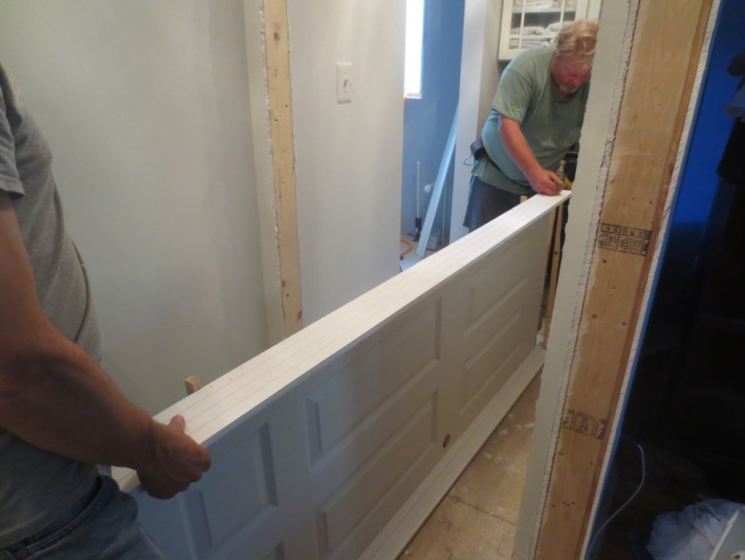 The door to the bathroom is a 6-panel door which opens toward the linen closet.