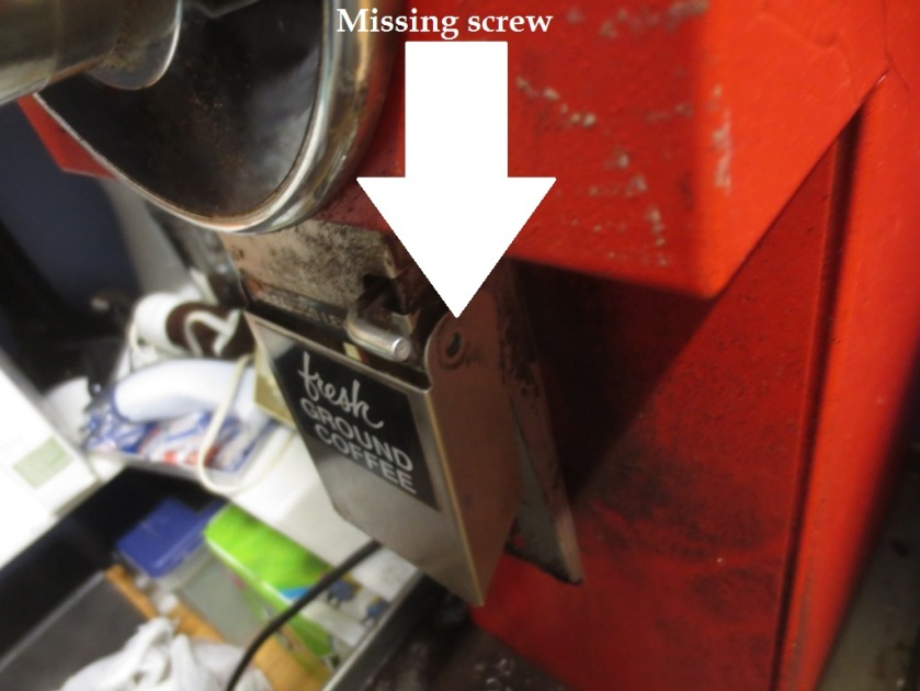 The screw on one side of the grinder's cleaning chute was missing.