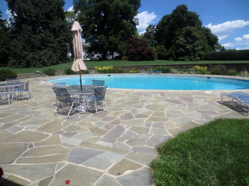 The natural stone deck complements the stone wall around the garden.