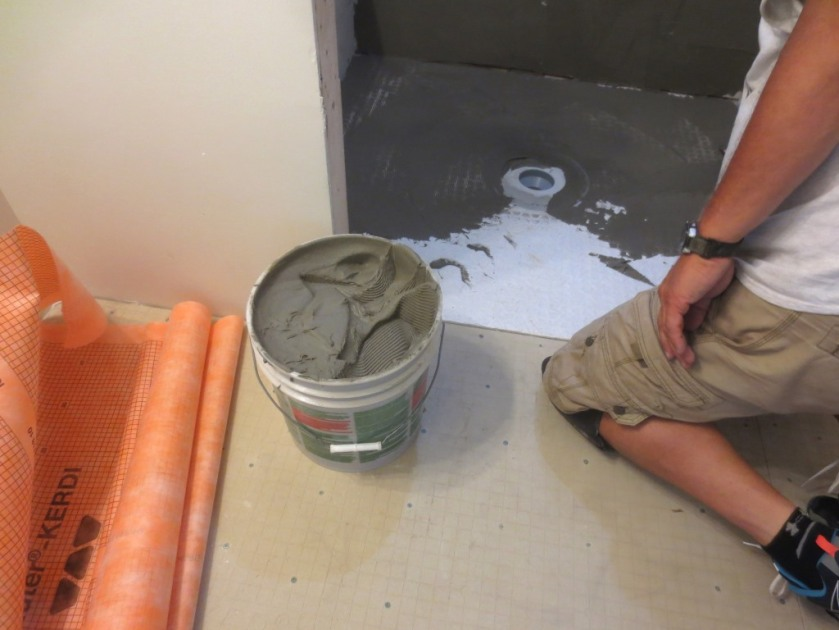 Pre-mixed thinset is used to hold the waterproofing in place.