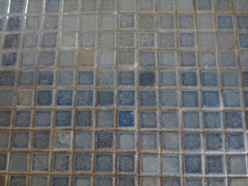 Variegated blue and grey tiles with grey grout.
