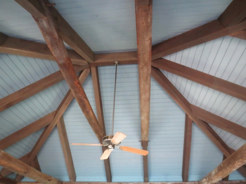 Tall paneled ceiling with rustic rafters and a fan to keep the air circulating.