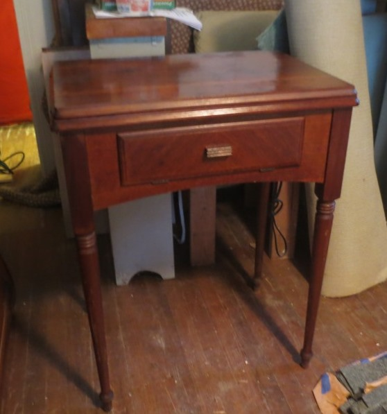 The vintage Singer sewing machine resides in a sturdy lift-top table.